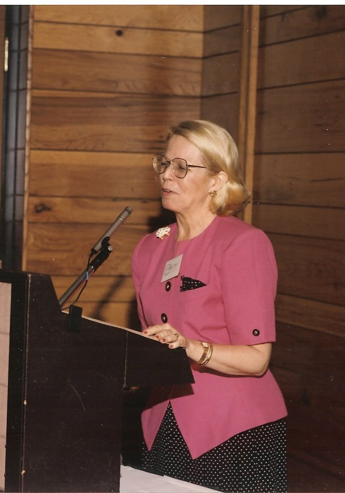 MaryLee Davis speaking in front of a large audiance